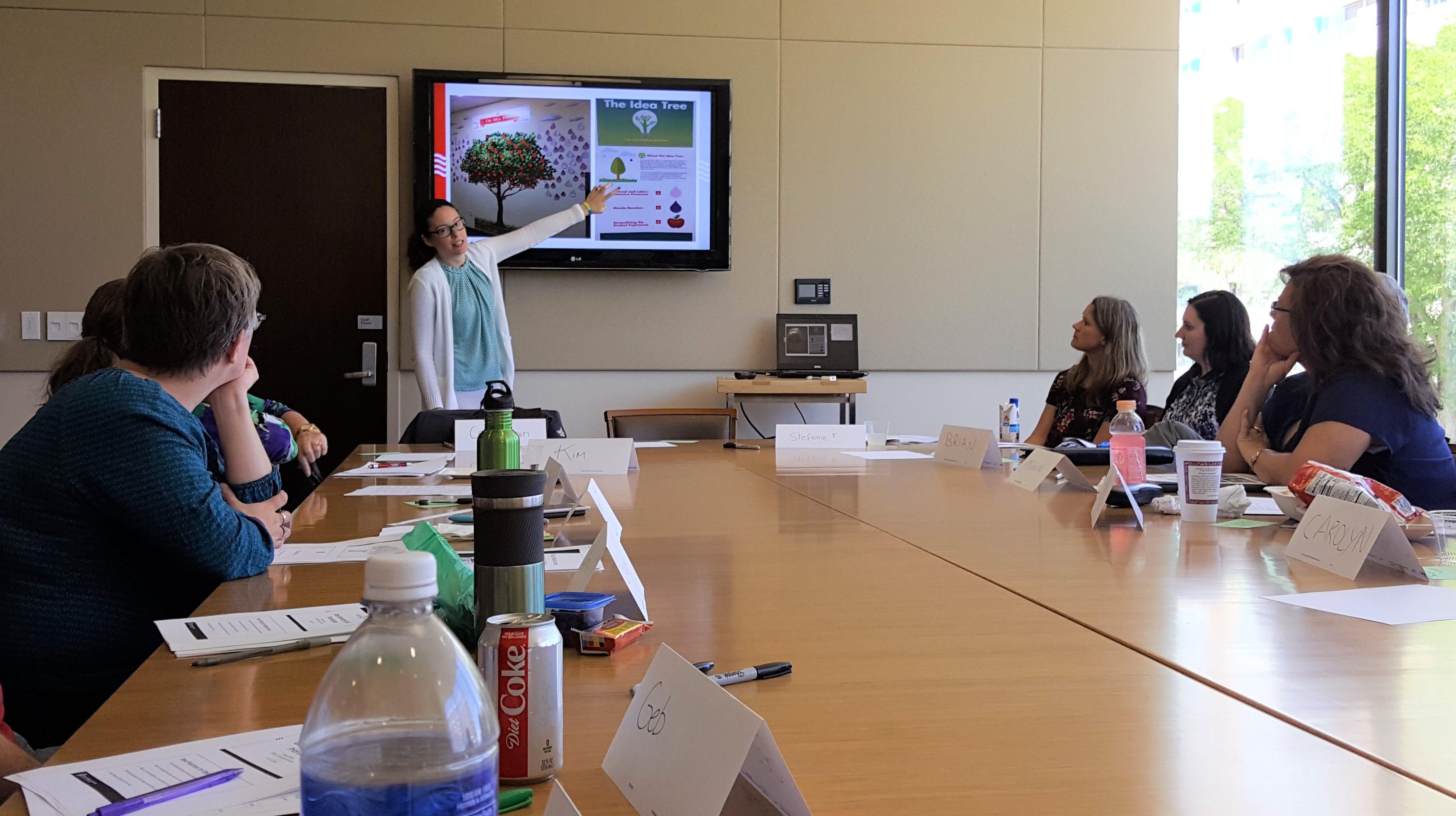 Cori Splain pointing to a slide showing an idea tree.